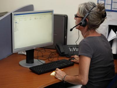 Femme au téléphone qui porte assistance à un senior